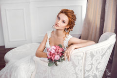 Bride in beautiful dress sitting resting on sofa indoors. Bride in beautiful dress sitting on sofa indoors with bouquet of flowers in white studio interior like Royalty Free Stock Photo