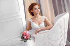 Bride in beautiful dress sitting resting on sofa indoors. Bride in beautiful dress sitting on sofa indoors with bouquet of flowers in white studio interior like Stock Photos