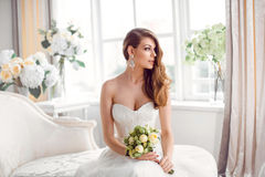 Bride in beautiful dress sitting resting on sofa indoors stock images