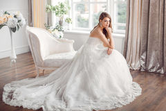 Bride in beautiful dress sitting resting on sofa indoors. Wedding. Bride in beautiful dress sitting on sofa indoors in white studio interior like at home. Trendy Royalty Free Stock Photography