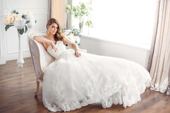 Bride in beautiful dress sitting resting on sofa indoors Royalty Free Stock Photography