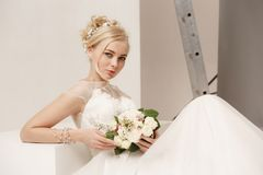 Bride in beautiful dress standing indoors in white studio interior like at home. Trendy wedding style shot. Young. Bride in beautiful dress standing indoors in Stock Photos