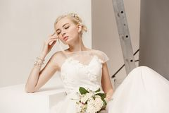 Bride in beautiful dress standing indoors in white studio interior like at home. Trendy wedding style shot. Young. Bride in beautiful dress standing indoors in Stock Images