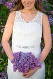 Bride with beautiful lilac flowers in hands Royalty Free Stock Image