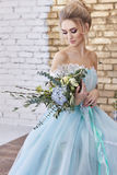 Bride in a beautiful turquoise dress in anticipation of wedding. Blonde in lace dress sea green with a bouquet . Happy bride Royalty Free Stock Photos