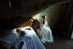 Beautiful sexy redhair lady in elegant white wedding dress. Fashion portrait of model indoors. Beauty woman sitting near her bed. Bride in a beautiful wedding Stock Photos