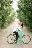 Bride and groom sit on bicycle on forest road, embrace and kiss. Stock Photo