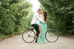 Bride and groom sit on bicycle on forest road, embrace, laugh an Stock Image