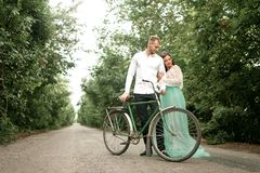 Bride and groom stand next to bicycle on forest road. Stock Image