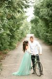 Bride and groom stand next to bicycle on forest road. Royalty Free Stock Photo