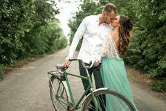 Bride and groom stand next to bicycle on forest road and kiss. C Royalty Free Stock Images