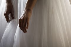 A bride in a beautiful wedding dress holding dress hem stock image