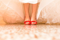Bride in a beautiful wedding dress putting on shoes Royalty Free Stock Image