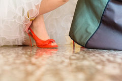Bride in a beautiful wedding dress putting on shoes Royalty Free Stock Photo