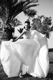 Bride in beautiful wedding long dress, young woman outdoor. With palms and sunny blue sky, dancing Royalty Free Stock Photography