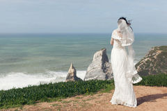 Bride in a beautiful white dress on a cliff by the ocean Stock Photos