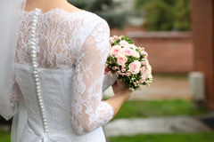 Bride in a beautiful white wedding dress with lace and pearls, s. Tands with her back and holds a wedding bouquet of roses in her hands. Horizontal shot Royalty Free Stock Photography