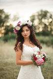 Bride. Beautiful young blond woman in the park with flower wreath and bouquet on a warm summer day Stock Photos