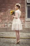 Bride. Beautiful young bride posing in a wedding dress in a retro cobble street, holding a sunflower bouquet royalty free stock photo