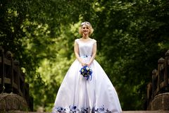 Bride in beauty wedding dress standing on bridge Stock Photo