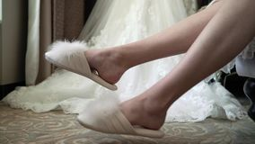 Bride in bedroom in slippers. Wedding dress at background stock footage