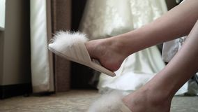 Bride in bedroom in slippers. Wedding dress at background stock video
