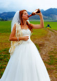 Bride with a beer bottle and a groom on bicycle on the background - wedding concept. Royalty Free Stock Images