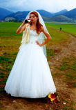 Bride with a beer bottle and a groom on bicycle on the background - wedding concept. Royalty Free Stock Photo