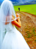 Bride with a beer bottle and a groom on bicycle on the background - wedding concept. Stock Photo