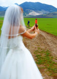 Bride with a beer bottle and a groom on bicycle on the background - wedding concept. Stock Image