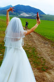 Bride with a beer bottle and a groom on bicycle on the background - wedding concept. Royalty Free Stock Photography