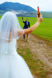 Bride with a beer bottle and a groom on bicycle on the background - wedding concept. Royalty Free Stock Image