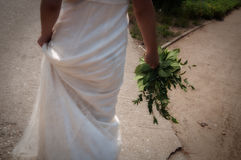 Bride from behind walking on a path Royalty Free Stock Image