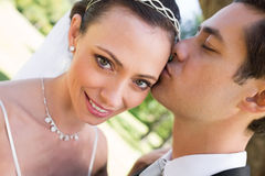 Bride being kissed by groom in garden Stock Photo