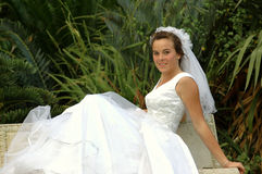 Bride on bench. A beautiful brunette caucasian bride head portrait with happy expression in her pretty face sitting casual and relaxed on a bench in the park royalty free stock images