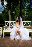 Bride on bench in park Stock Photo