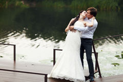 Bride bends over a groom kissing him on the river berth Stock Photography