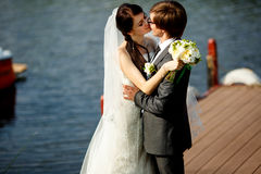 Bride bends over a groom kissing him on the river berth Royalty Free Stock Image