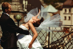 Bride bends over in groom`s hands and her veil spreads around Stock Photos