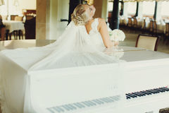 Bride bends over a piano and her veil spreads over it Stock Photo