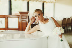 Bride bends over a piano and holds her head with a hand Stock Photography