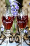 Bride besides groom. Glass long stem champaign glasses with edged bells and the words bride and groom.  Lilac flowers on stems and in rear Stock Photo