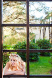 Bride and a big frame of the window. Young bride looking through the window fram Stock Photos
