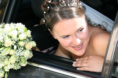 Bride in black car. The bride looks out from a window black car. She holds a wedding bouquet Stock Image
