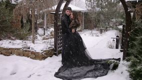 Wedding. Bride in a black dress. Gothic wedding. The bride in a black dress is embracing with the groom in a heavy snowfall in a wooden arch. Wedding. Bride in stock video