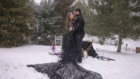 Bride in a black dress. Gothic wedding. Winter. The bride and the groom in black standing in the woods under a heavy snowfall on the background of decorated stock video footage