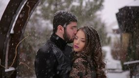 Bride in a black dress. Gothic wedding. Winter. A young couple dressed in gothic black style posing for a camera in the winter in a park with a heavy snowfall stock video footage