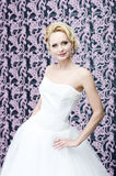 Bride blonde portrait. 20s yeared blonde bride posing in white wedding dress. She is slightly smiling Stock Photo