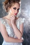 Bride blonde woman in a modern color wedding dress with elegant hair style and make up. Fashion beauty portrait. Over textured background stock photography