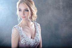 Bride blonde woman in a modern color wedding dress with elegant hair style and make up. Fashion beauty portrait. Over textured background stock image